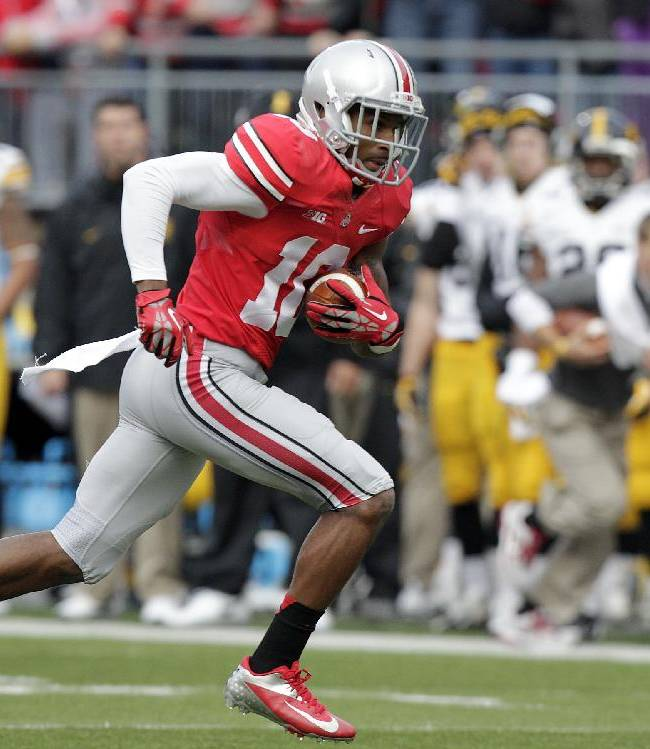 In this Saturday, Oct. 19, 2013, file photo, Ohio State wide receiver Corey Brown runs against Iowa during an NCAA college football game in Columbus, Ohio. Brown was a good player for Ohio State a year ago. But he wasn't completely committed. His head coach said he wouldn't even walk across the street for him. But Brown has come full circle, as evidenced by his stirring, adults-only halftime speech last week which lifted the Buckeyes to yet another victory