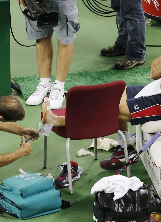 Janko Tipsarevic of Serbia, right, receives the medical treatment during the match against Marcel Granollers of Spain at their first round of the Shanghai Masters tennis tournament at Qizhong Forest Sports City Tennis Center in Shanghai, China, Monday, Oct. 7, 2013. Granollers won 6-4, 6-4