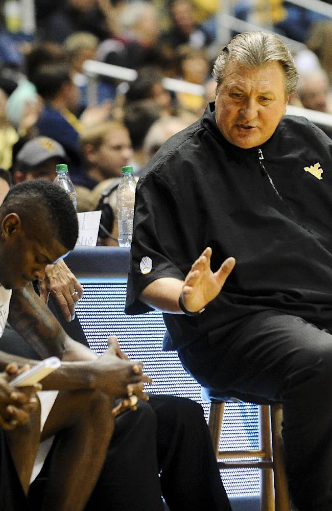 West Virginia's Bob Huggins speaks Eron Harris after coming off the floor during the second half of an NCAA college basketball exhibition game at WVU Coliseum in Morgantown, W.Va., on Monday, Nov. 4, 2013. West Virginia won 89-70