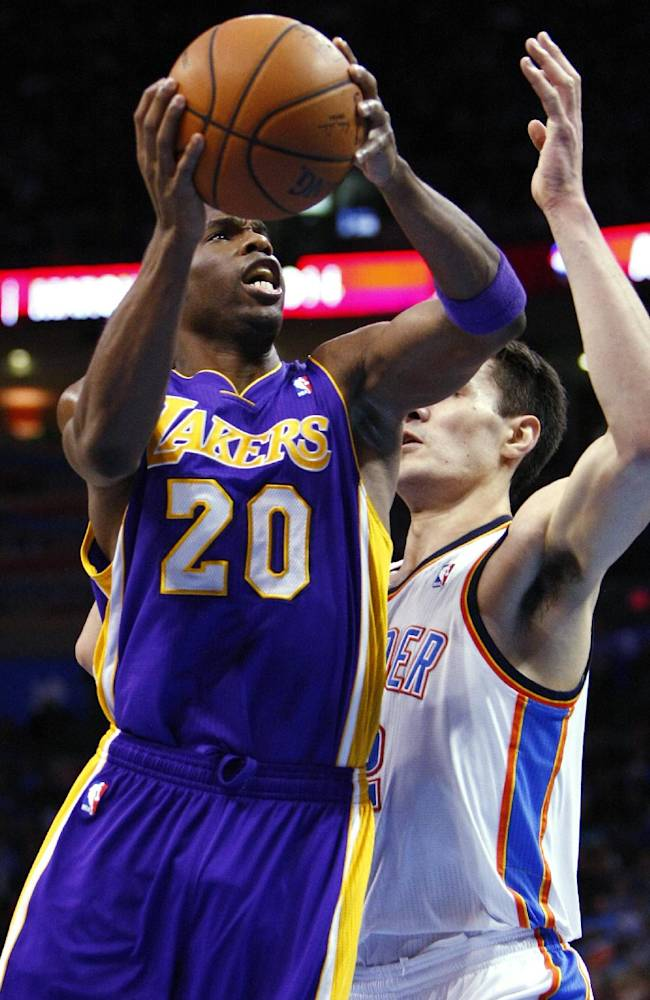 Los Angeles Lakers guard Jodie Meeks (20) goes up for a shot in front of Oklahoma City Thunder center Steven Adams during the first half of an NBA basketball game in Oklahoma City, Thursday, March 13, 2014. Oklahoma City won 131-102