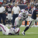 Houston Texans' Ryan Fitzpatrick (14) tries to escape Buffalo Bills defenders Kyle Williams (95) and Marcell Dareus (99) during the third quarter of an NFL football game, Sunday, Sept. 28, 2014, in Houston. The Associated Press