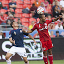 Toronto FC's Justin Morrow heads the ball while pushing away Chivas USA's Donny Tola during the second half of an MLS soccer game in Toronto on Sunday, Sept. 21, 2014 The Associated Press