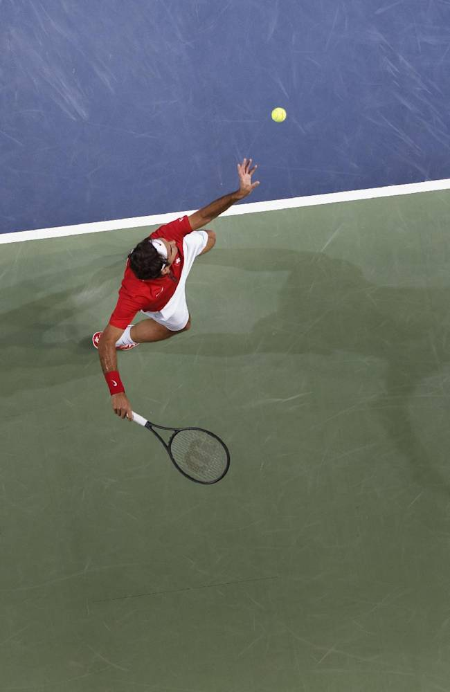 Roger Federer of Switzerland serves a ball to Mikhail Kukushkin of Kazakhstan during the second single match of the Davis Cup World Group Quarterfinal match between Switzerland and Kazakhstan in Geneva, Switzerland, Friday, April 4, 2014