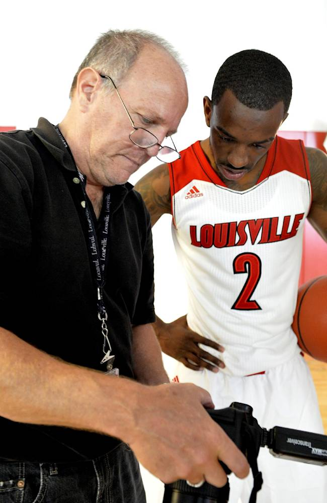 University of Louisville team photographer Jeff Reinking, left, shows Louisville's Russ Smith his photo during Louisville's NCAA college basketball media day, Saturday, Oct. 12, 2013, in Louisville, Ky