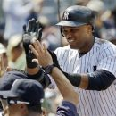 New York Yankees Robinson Cano is greeted at the dugout steps after hitting a third-inning, two-run home run during their baseball game against the Chicago White Sox at Yankee Stadium in New York, Sunday, July 1, 2012.  (AP Photo/Kathy Willens)