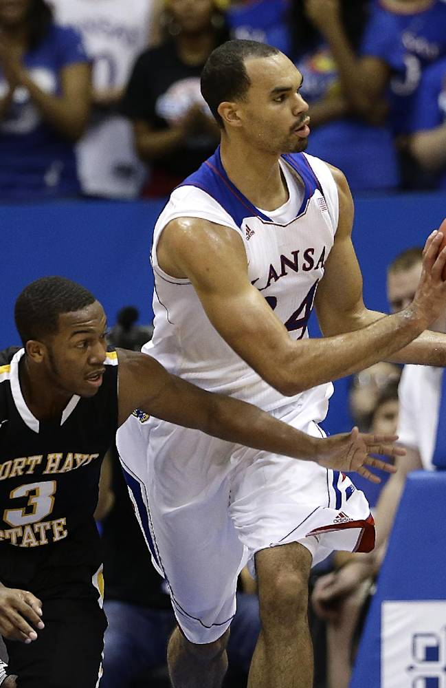 Kansas' Perry Ellis passes the ball away under pressure from Fort Hays State's Craig Nicholson (3) during the first half of an exhibition NCAA college basketball game Tuesday, Nov. 5, 2013, in Lawrence, Kan