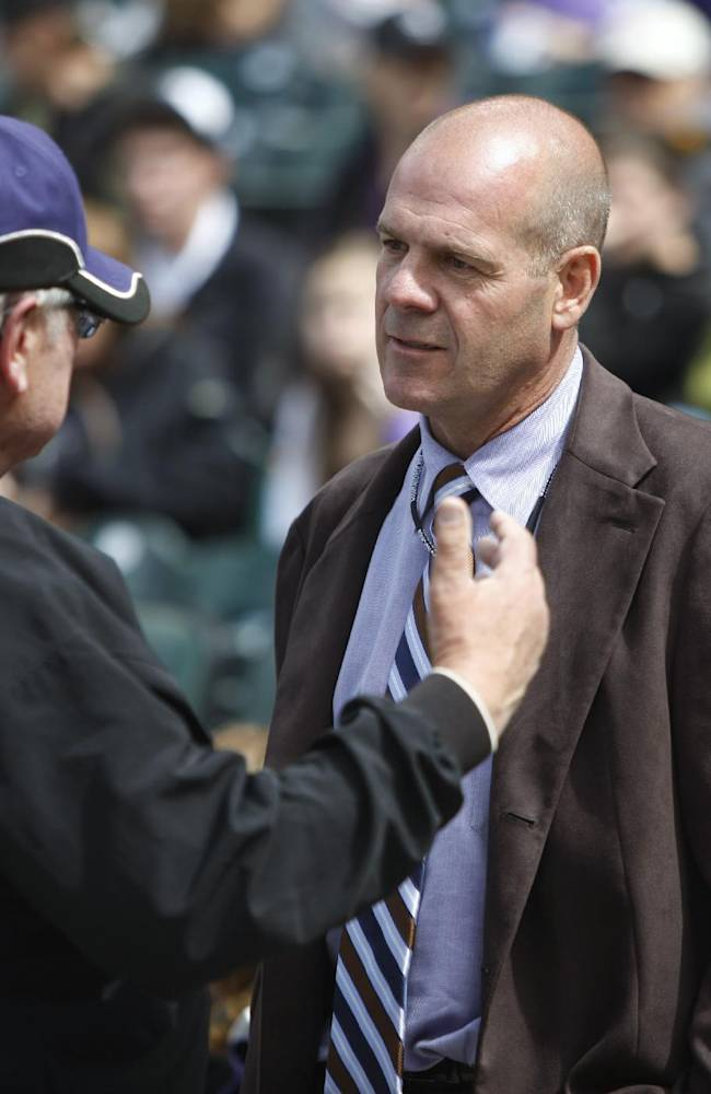 In this April 25, 2010, photo, Colorado Rockies co-owner Charlie Monfort, right, chats with a security worker before the Rockies played the Florida Marlins in baseball game in Denver. Monfort has been arrested on suspicion of driving under the influence of alcohol and speeding. The Greeley Tribune reports Monfort was arrested late Monday, Nov. 4, 2013, in Windsor, about 60 miles north of Denver