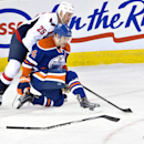 Washington Capitals' Jason Chimera (25) breaks his stick while battling for the puck with Edmonton Oilers' Taylor Hall (4) during second-period NHL hockey game action in Edmonton, Alberta, Wednesday, Oct. 22, 2014 The Associated Press