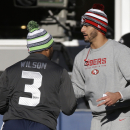 Seattle Seahawks quarterback Russell Wilson, left, shakes hands with San Francisco 49ers quarterback Colin Kaepernick, right, before an NFL football game, Sunday, Dec. 14, 2014, in Seattle The Associated Press