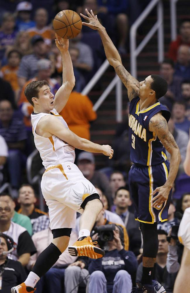 Phoenix Suns' Goran Dragic, left, of Slovenia, tries to get off a pass as Indiana Pacers' George Hill (3) jumps to defend during the first half of an NBA basketball game Wednesday, Jan. 22, 2014, in Phoenix.  The Suns defeated the Pacers 124-100