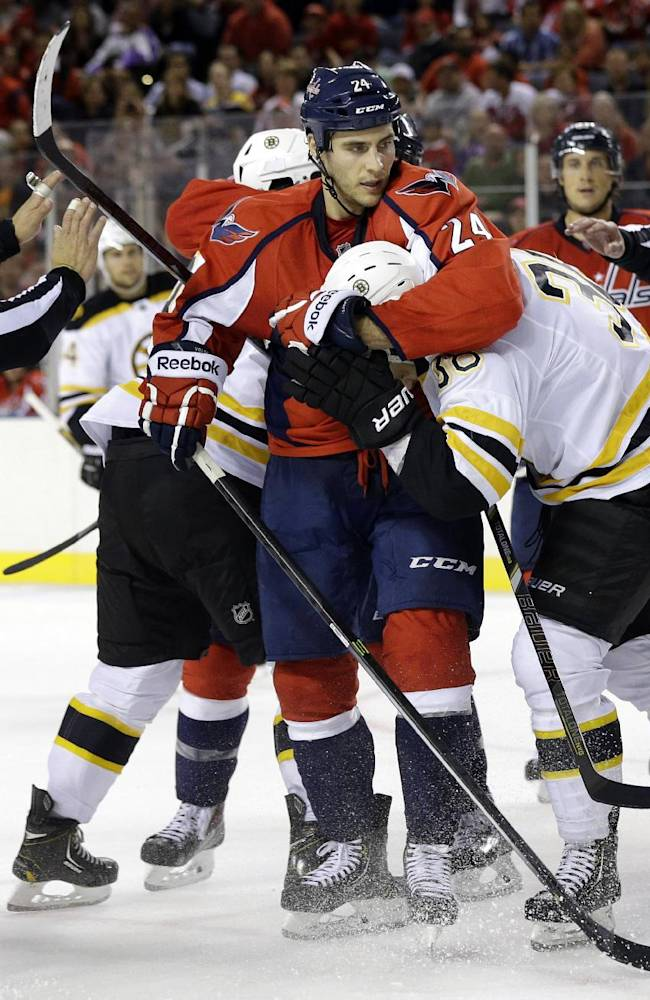 Officials break up a scuffle between Washington Capitals left wing Aaron Volpatti (24) and Boston Bruins left wing Jordan Caron in the third period of a preseason NHL hockey game, Tuesday, Sept. 17, 2013, in Baltimore