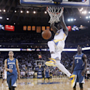 Golden State Warriors' Draymond Green, center, dunks over Minnesota Timberwolves' Kevin Martin (23) and Gorgui Dieng (5) during the second half of an NBA basketball game on Monday, April 14, 2014, in Oakland, Calif. Golden State won 130-120 The Associated