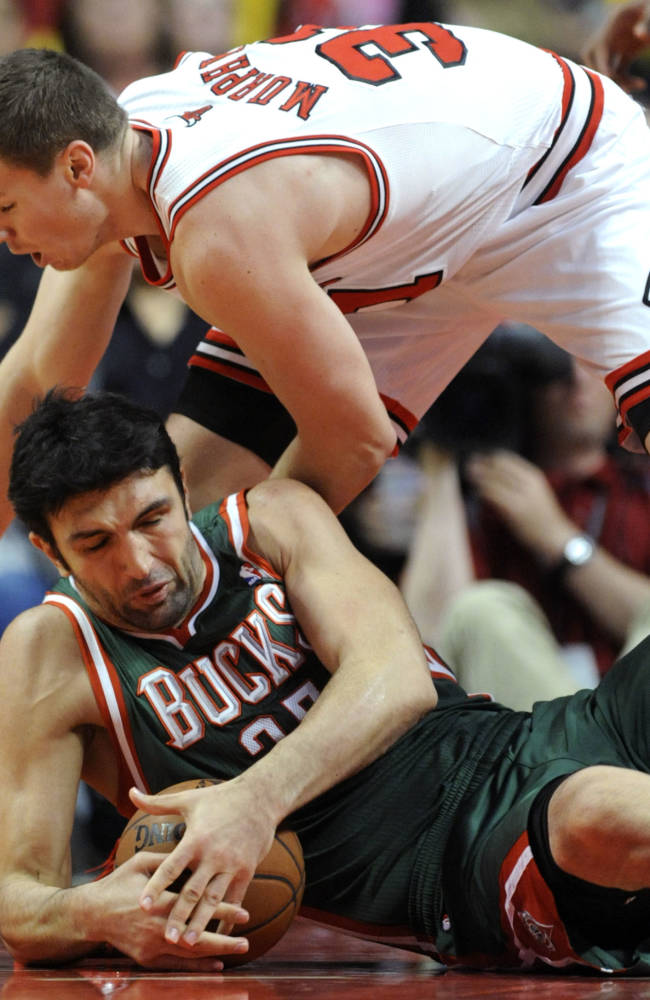 Milwaukee Bucks' Zaza Pachulia of Georgia, (27), battles Chicago Bulls' Erik Murphy (31), for a loose ball during the second half of an NBA preseason basketball game in Chicago, Monday, Oct. 21, 2013. Chicago won 105-84