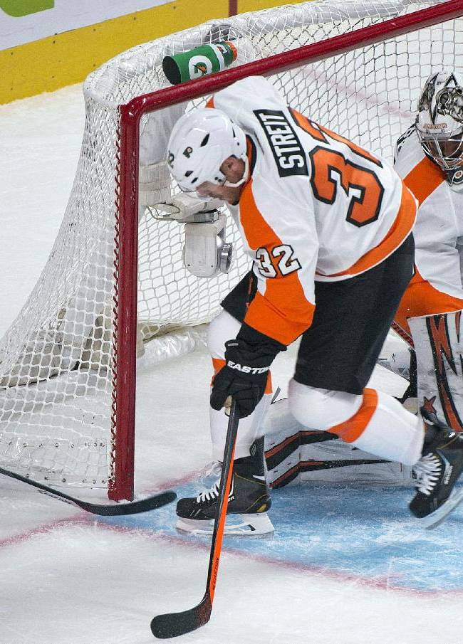 Montreal Canadiens' Brian Gionta, left, scores against Philadelphia Flyers goaltender Ray Emery, right, as Flyers' Mark Streit defends during the first period of an NHL hockey game in Montreal, Saturday, Oct. 5, 2013
