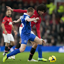 Manchester United's Marouane Fellaini, right, fights for the ball against Everton's James McCarthy during their English Premier League soccer match at Old Trafford Stadium, Manchester, England, Wednesday Dec. 4, 2013