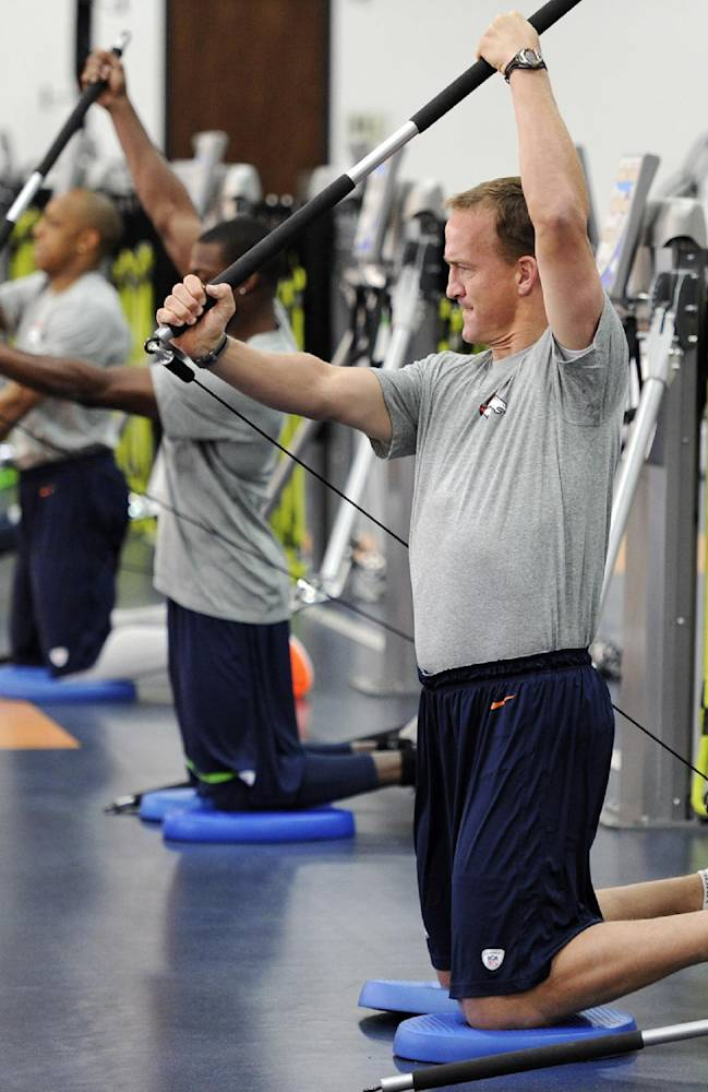 In this photo provided by the Denver Broncos, quarterback Peyton Manning, right, and other offensive players work during the first phase of the offseason training program at the NFL football teams training facility in Englewood, Colo., on Monday, April 21, 2014