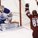 Arizona Coyotes' Mikkel Boedker (89), of Denmark, scores the first of two goals in the third period against Edmonton Oilers' Ben Scrivens (30) of an NHL hockey game Wednesday, Oct. 15, 2014, in Glendale, Ariz. The Coyotes' Boedker ended up with a hat tri