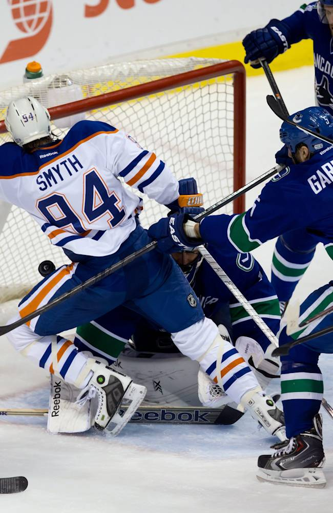 The puck stays out of the goal as Vancouver Canucks' Jason Garrison, right, checks Edmonton Oilers' Ryan Smyth, left, in front of goalie goalie Roberto Luongo as Alexander Edler, top right, of Sweden, watches during second period NHL hockey action  in Vancouver, Canada, Sunday, Jan. 27, 2014