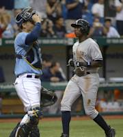 New York Yankees' Alfonso Soriano, right, scores from third base on Curtis Granderson's sacrifice fly during the 11th inning of a baseball game as Tampa Bay Rays catcher Jose Lobaton watches in St. Petersburg, Fla., Sunday, Aug. 25, 2013. The Yankees won 3-2. (AP Photo/Phelan M. Ebenhack)