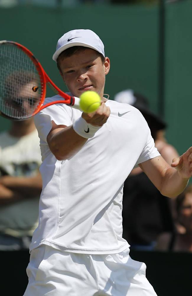 Stefan Kozlov of the U.S. plays a return to Hyeon Chung of South Korea during their boys' singles quarterfinal match at the All England Lawn Tennis Championships in Wimbledon, London, Friday, July 4, 2014