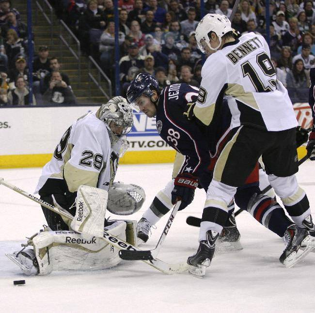 Pittsburgh Penguins goalie Marc-Andre Fleury (29) blocks a shot by Columbus Blue Jackets' Boone Jenner (38) during the second period of an NHL hockey game, Friday, March 28, 2014, in Columbus, Ohio. Also defending is Beau Bennett (19)