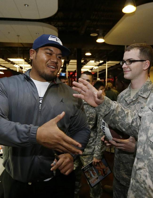 Seattle Seahawks NFL football practice squad player Sealver Siliga, left, shakes hands with troops at Joint Base Lewis-McChord, Wash., Tuesday, Sept. 10, 2013, following a ceremony to transfer the team's 12th Man Flag from U.S. Army soldiers who have returned from Afghanistan to U.S. Air Force air crews who fly cargo planes worldwide