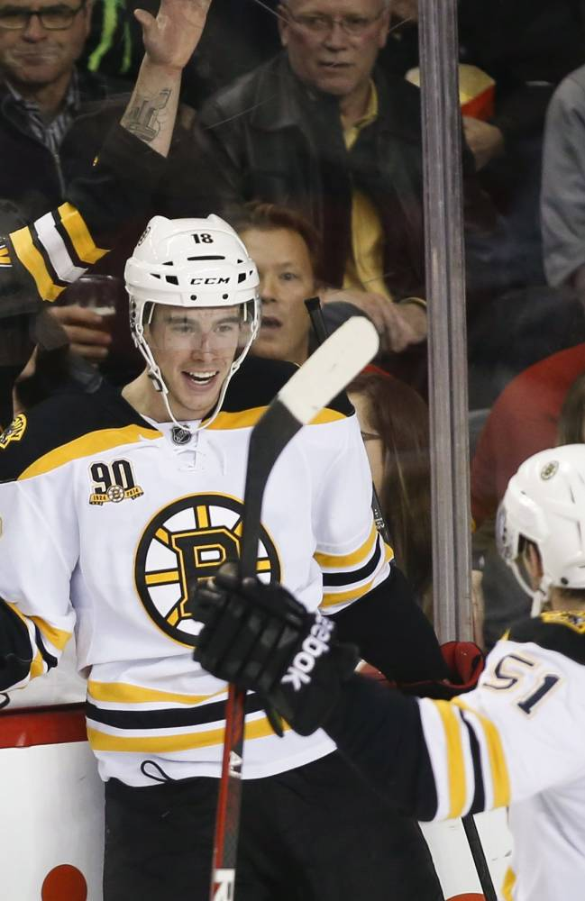 Boston Bruins' Reilly Smith, left, celebrates his game winning goal with teammate Ryan Spooner during third period NHL hockey action against the Calgary Flames in Calgary, Alberta, Tuesday, Dec. 10, 2013