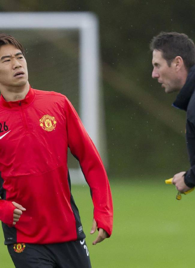 Manchester United's Shinji Kagawa, left, trains with teammates at Carrington training ground in Manchester, Tuesday, Oct. 22, 2013. Manchester United will play Real Sociedad in a Champion's League Group A soccer match on Wednesday