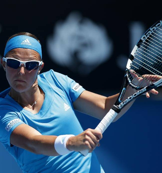 Kirsten Flipkens of Belgium makes a backhand return to Laura Robson of Britain during their first round match at the Australian Open tennis championship in Melbourne, Australia, Monday, Jan. 13, 2014