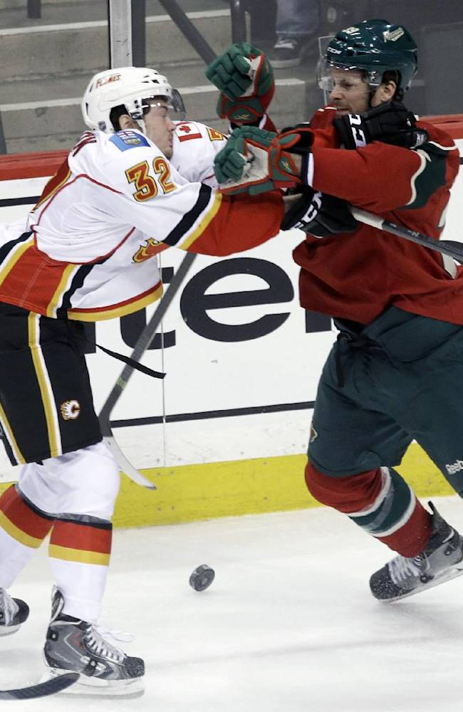 Calgary Flames' Paul Byron, left, and Minnesota Wild's Nate Prosser do some shoving as the puck rolls between them in the first period of an NHL hockey game, Monday, March 3, 2014, in St. Paul, Minn