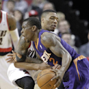 Phoenix Suns guard Eric Bledsoe, left, drives against Portland Trail Blazers guard Damian Lillard during the second half of an NBA basketball game in Portland, Ore., Friday, April 4, 2014. Bledsoe scored 30 points as they beat the Trail Blazers 109-93 Th