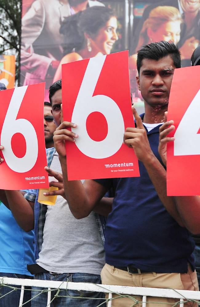 Cricket spectators hold up the prison number of former president Nelson Mandela 's at the ODI cricket match between South Africa and India in Durban South Africa, Sunday, Dec. 8, 2013.  A minutes silence was held to honour Mandela's passing Thursday after a long illness. (AP Photo)