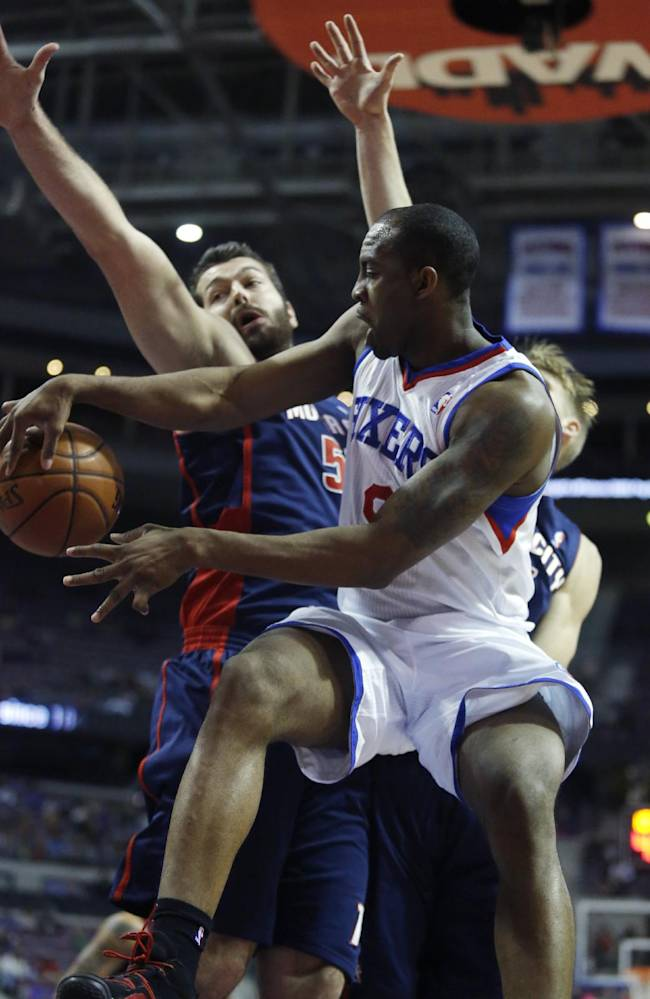 Philadelphia 76ers guard James Anderson, right, passes the ball against Detroit Pistons forward Josh Harrellson, left, during the first half of an NBA basketball game on Sunday, Dec. 1, 2013, in Auburn Hills, Mich