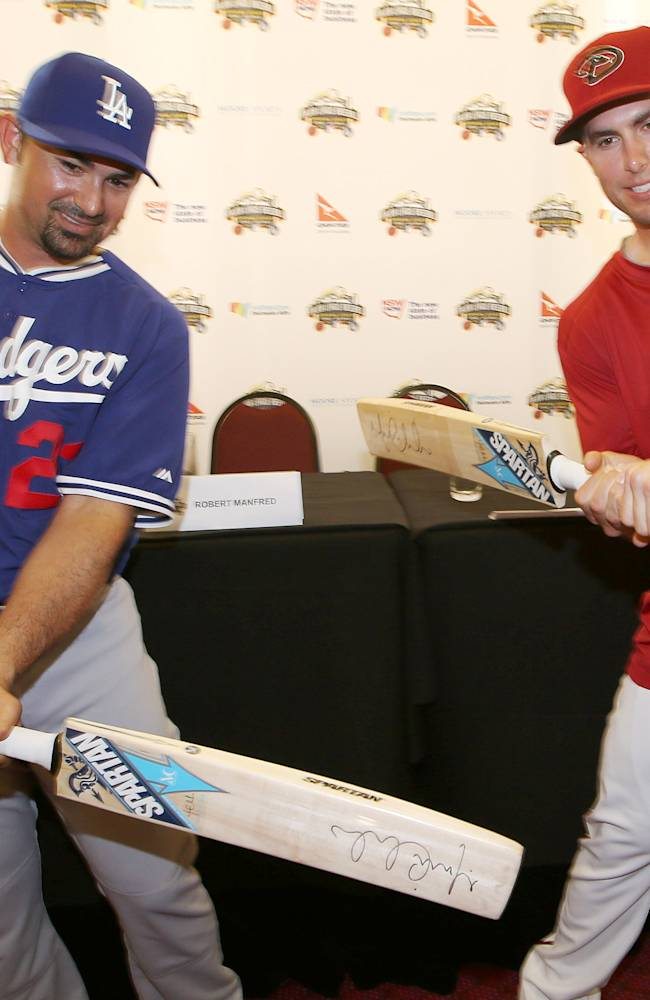 The Los Angeles Dodgers' Adrian Gonzalez, left, and The Arizona Diamondbacks' Paul Goldschmidt try swinging cricket bats at the Sydney Cricket Ground in Sydney, Tuesday, March 18, 2014. The MLB season-opening two-game series between the Los Angeles Dodgers and Arizona Diamondbacks in Sydney will be played this weekend