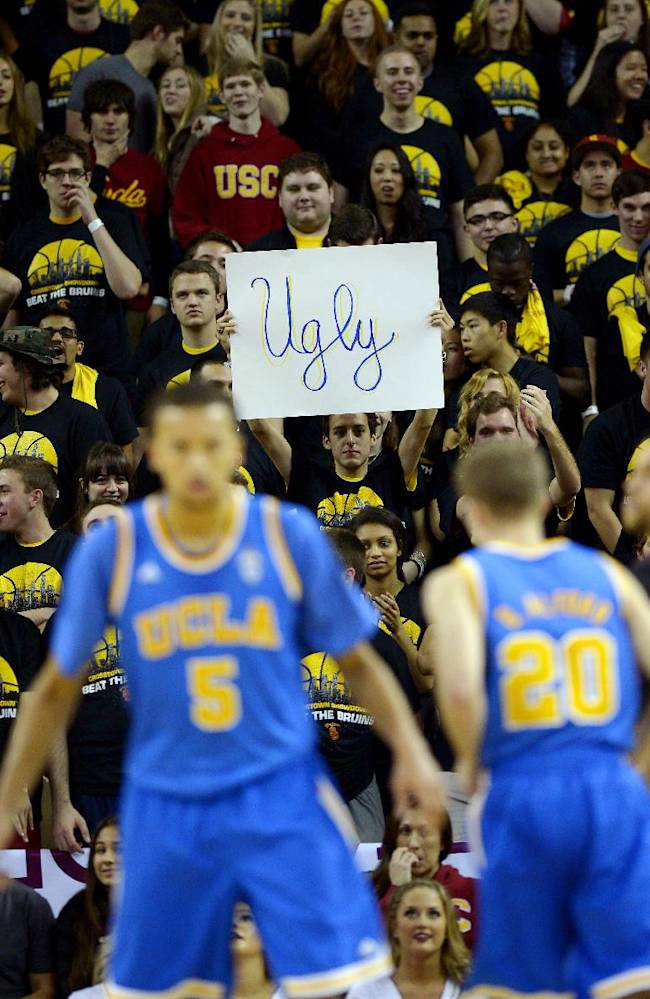 A Southern California fan holds up a sign as UCLA guard Kyle Anderson, left, and guard Bryce Alford during the first half of an NCAA college basketball game against Southern California, Saturday, Feb. 8, 2014, in Los Angeles