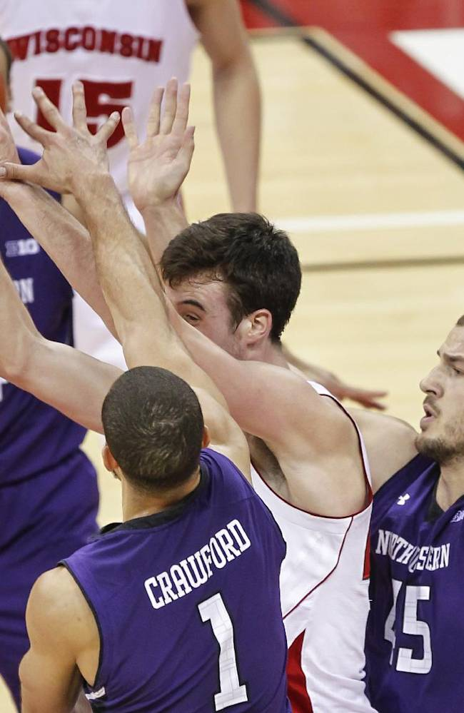 Northwestern's Drew Crawford (1) and Nikola Cerina (45) trap Wisconsin's Frank Kaminsky during the second half of an NCAA college basketball game Wednesday, Jan. 29, 2014, in Madison, Wis. Northwestern upset Wisconsin, 65-56