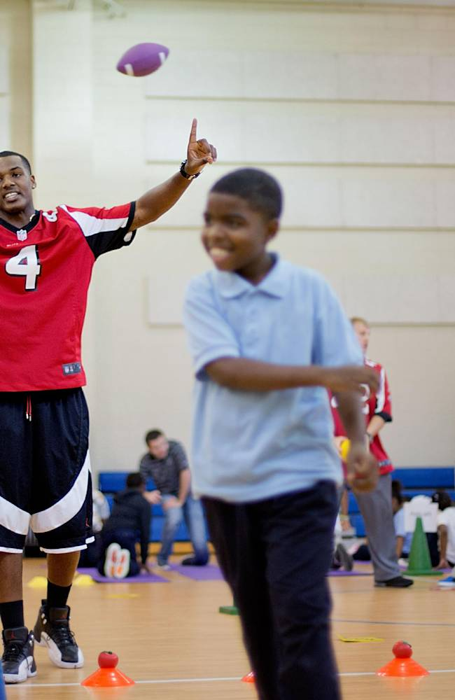 Atlanta Falcons' Dominique Davis (4) conducts a drill with students from M. Agnes Jones Elementary School as the NFL football team takes part in the volunteer project,