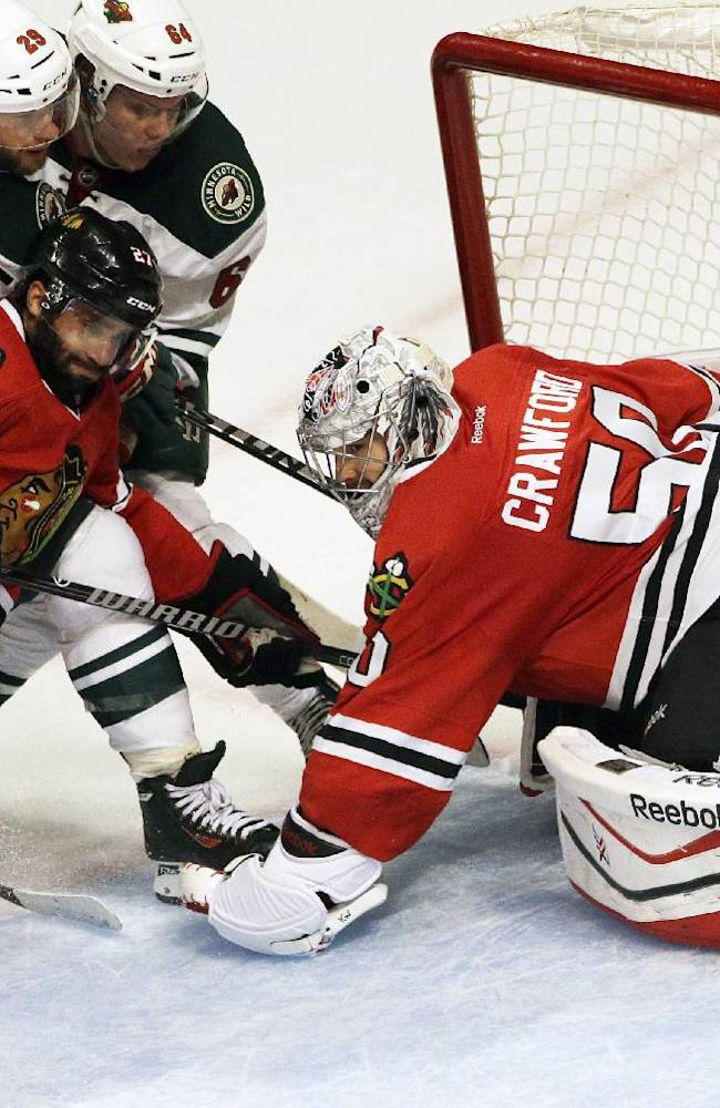 Chicago Blackhawks goalie Corey Crawford (50) blocks a shot as Johnny Oduya (27) battles for the puck against Minnesota Wild's Jason Pominville (29) and Mikael Granlund (64) during the third period in Game 5 of an NHL hockey second-round playoff series in Chicago, Sunday, May 11, 2014. The Blackhawks won 2-1
