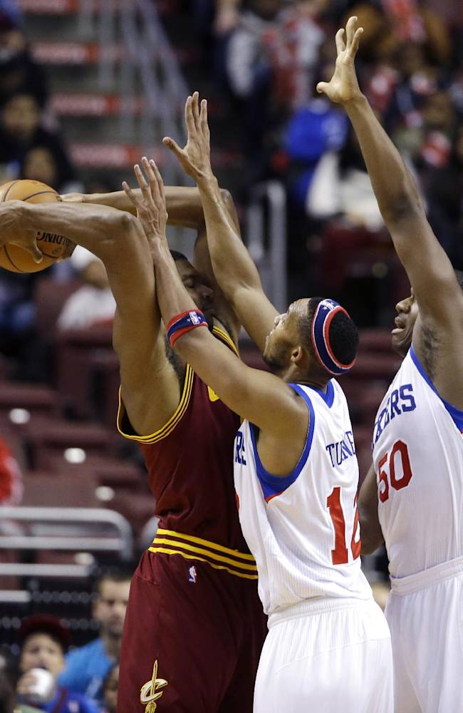 Cleveland Cavaliers' Andrew Bynum, left, tries to keep the ball away from Philadelphia 76ers' Evan Turner, center, and Lavoy Allen during the second half of an NBA basketball game, Friday, Nov. 8, 2013, in Philadelphia. Philadelphia won 94-79