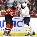 New Jersey Devils center Ryan Carter, left, and Buffalo Sabres left wing Marcus Foligno fight during the first period of an NHL hockey game, Saturday, Nov. 30, 2013, in Newark, N.J The Associated Press
