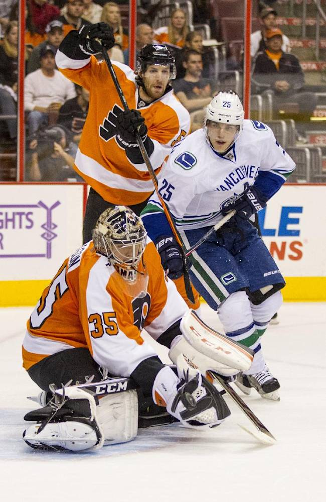 Philadelphia Flyers' Steve Mason (35) stops the shot with his glove while teammate Braydon Coburn, top left, deals with Vancouver Canucks' Mike Santorelli during the first period of an NHL hockey game, Tuesday, Oct. 15, 2013, in Philadelphia