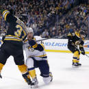 Boston Bruins center Patrice Bergeron (37) passes the puck by Nashville Predators defenseman Mattias Ekholm (14) to teammate left wing Brad Marchand, right, who scores a goal in the second period of an NHL hockey game in Boston, Tuesday, Dec. 23, 2014. (AP Photo/Elise Amendola)