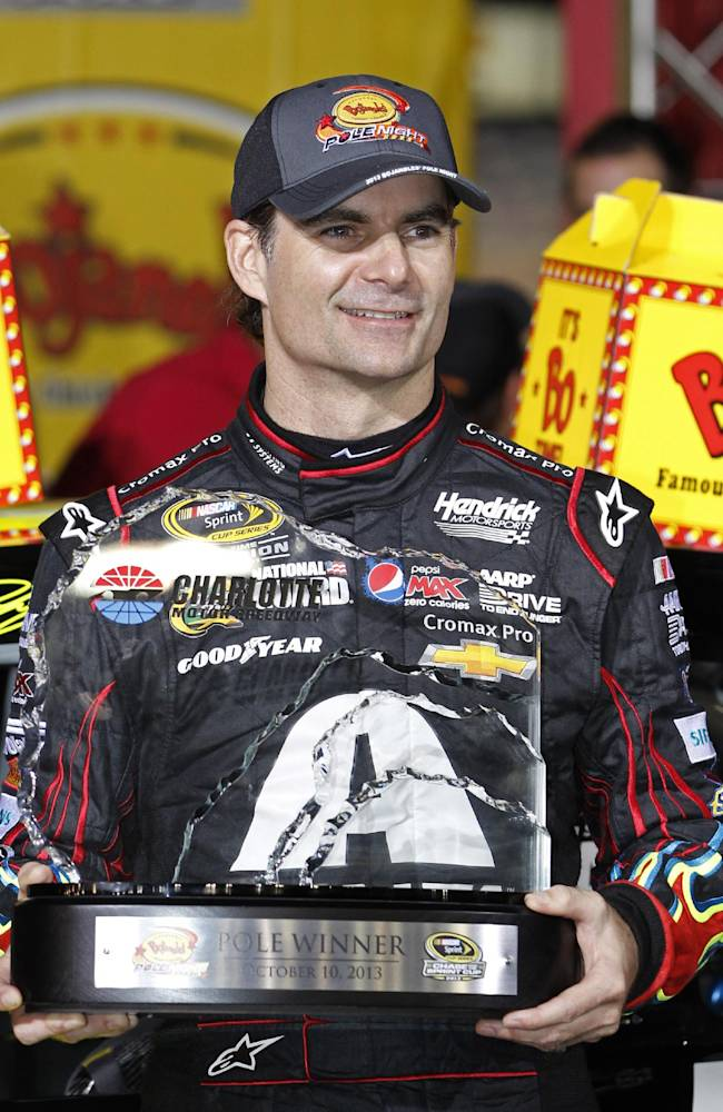 Jeff Gordon holds the trophy in victory lane after winning the pole position for Saturday's NASCAR Sprint Cup series auto race during qualifying at Charlotte Motor Speedway in Concord, N.C., Thursday, Oct. 10, 2013