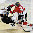 Chicago Blackhawks left wing Brandon Bollig, right, takes out Anaheim Ducks defenseman Ben Lovejoy during the third period of an NHL hockey game Friday, Dec. 6, 2013, in Chicago. The Ducks won 3-2 in a shootout The Associated Press