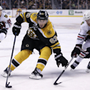 Boston Bruins left wing Brad Marchand (63) tries to edge out Chicago Blackhawks defenseman Duncan Keith (2) as he breaks towards the goal during the second period of an NHL game in Boston, Thursday, Dec. 11, 2014 The Associated Press