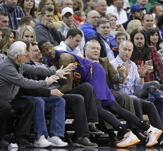Phoenix Suns' Archie Goodwin (20) lands in the crowd after chasing a loose ball in the second quarter of an NBA basketball game against the Utah Jazz Wednesday, Feb. 26, 2014, in Salt Lake City. The Jazz won 109-86