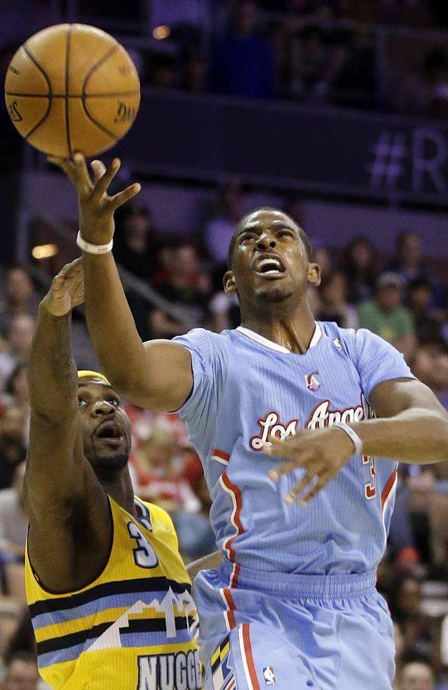 The Los Angeles Clippers' Chris Paul, right, shoots over the Denver Nuggets' Ty Lawson during the first half of a preseason NBA basketball game on Saturday, Oct. 19, 2013, in Las Vegas. The Clippers defeated the Nuggets in overtime 118-111