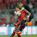 Manchester United's Nemanja Vidic, right, climbs on top of Bayern's Mario Mandzukic during the Champions League quarterfinal second leg soccer match between Bayern Munich and Manchester United in the Allianz Arena in Munich, Germany, Wednesday, April 9, 2