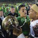 FILE - In this Jan. 1, 2015, file photo, Oregon quarterback Marcus Mariota, center left, greets Florida State quarterback Jameis Winston after Oregon's win in the Rose Bowl NCAA college football playoff semifinal game in Pasadena, Calif. There will be several noticeable absences when the three-day draft starts Thursday night, including potential top picks. Winston, Mariota and Alabama wide receiver Amari Cooper all plan to skip the spotlight. (AP Photo/Mark J. Terrill, File)