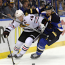 St. Louis Blues' Alex Pietrangelo (27) and Chicago Blackhawks' Jonathan Toews (19) battle for the puck during the first period in Game 2 of a first-round NHL hockey playoff series, Saturday, April 19, 2014, in St. Louis The Associated Press